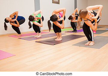 Chair twist pose in a yoga class - Large group of women...