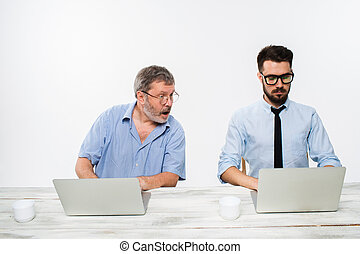 The two colleagues working together at office on white...