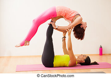 Trying out some acrobatic yoga - Profile view of a couple of...