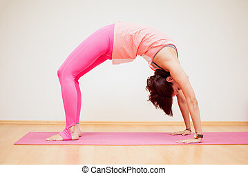 Backbend pose in a yoga studio - Young woman practicing a...