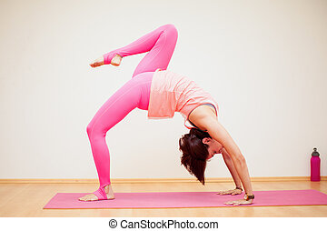 Backbend with raised leg yoga pose - Pretty young woman...