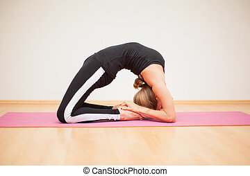 Backbend pose in a yoga studio - Cute caucasian flexible...