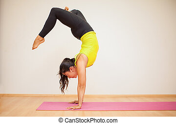 Headstand with crossed legs - Pretty brunette doing a...