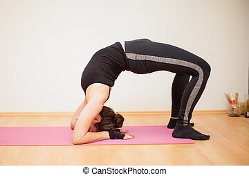 Practicing the backbend yoga pose - Athletic young woman...