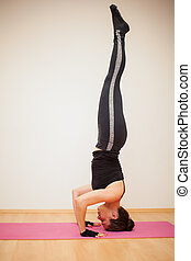 Headstand in a yoga studio - Profile view of a tall and...