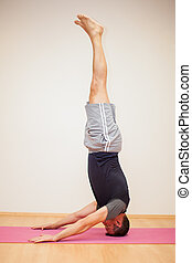 Headstand pose by a man - Profile view of a man doing a...