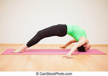 Strong woman doing yoga - Profile view of a young woman...