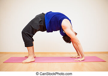Backbend pose by a young man - Portrait of a young man doing...