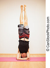 Headstand during yoga practice - Front view of a young man...