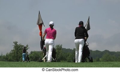 back view of two women walking down the golf course