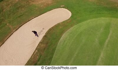 man hitting a golf ball out of a sand trap - aerial...