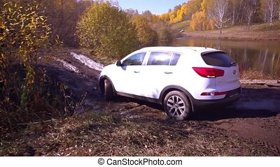 SUV got stuck in the mud and trying to go out in the autumn forest