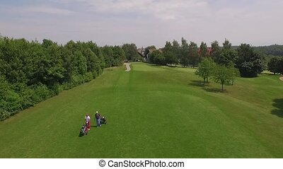 two persons walking at the golf course - drone flies above...