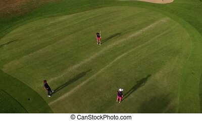 people playing golf - aerial perspective of three people...