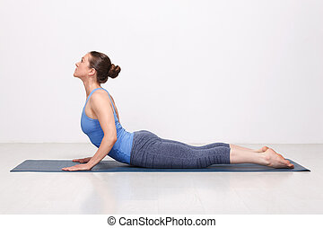 Sporty fit yogini woman practices yoga asana bhujangasana -...