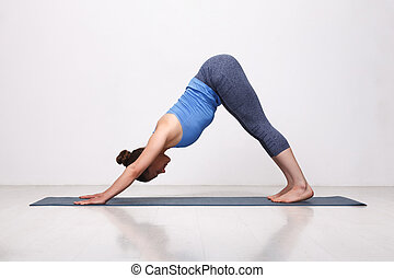Beautiful sporty fit yogi girl practices yoga asana...