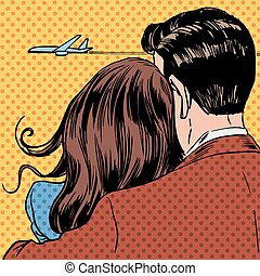 Loving couple looking at a plane taking off in the sky. A...