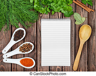 Spices recipe background. Variety of condiments with recipe sheet on old wooden table. Top view