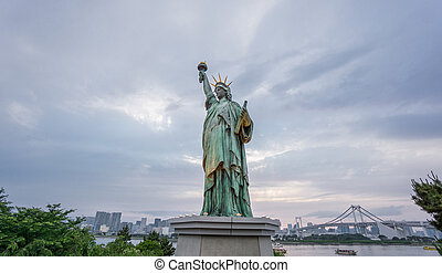 Statue of Liberty and Rainbow bridge in Odaiba at sunset