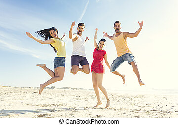 Friends Jump - Group of friends making a jump together at...