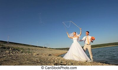 Wedding Fun - Bride and groom making soap bubbles on a lake
