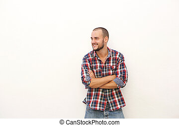 Smiling young man in plaid shirt standing with arms crossed