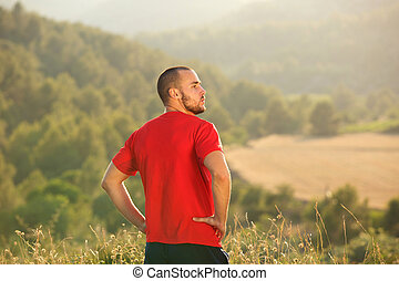 Healthy young man standing outside in nature