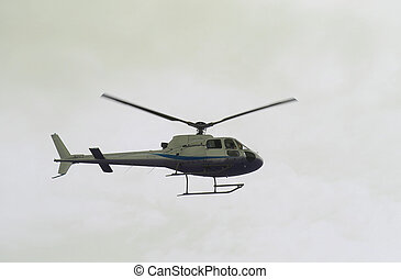 light civil helicopter flies in the sky and carries tourists