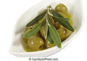 Green olives in olive oil with branch on a plate