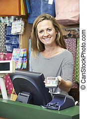 Female Cashier At Sales Desk With Credit Card Machine