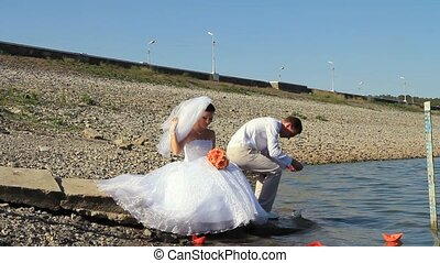 Symbol Of Journey - Bride and groom on a lake with paper...