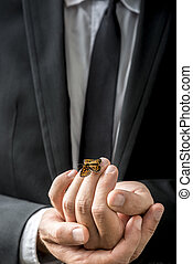 Businessman carefully holding a butterfly that has settled on his fingers