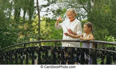 Granddaughter And Grandmother On A Bridge