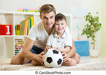 child boy with dad play football at home - child boy with...