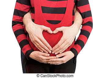 Heart from hands on the pregnant woman - The husband and the...