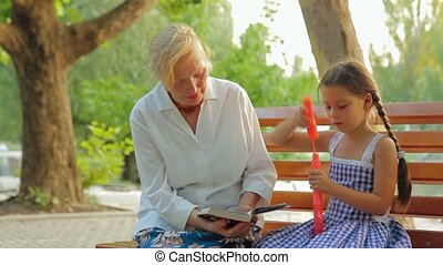 Family In A Park - Grandmother and granddaughter seating in...