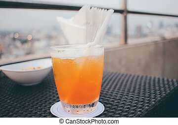 Cocktail glass in rooftop bar against city view