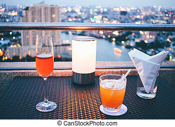 Cocktail glasses with candle light in rooftop bar against...