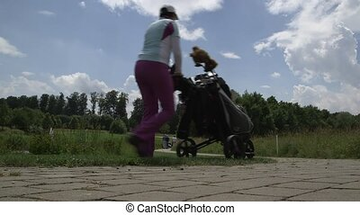 woman walks with her caddy to the next hole - woman walks...