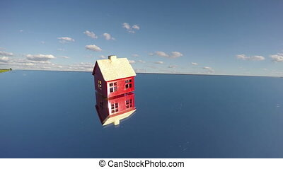small red house model on mirror