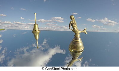 two antique brass bells on mirror in space and clouds motion...