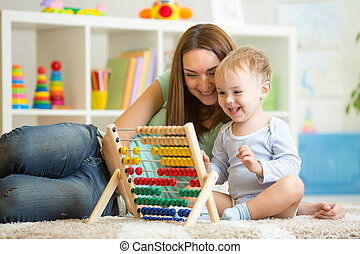 kid playing with abacus - kid and mother playing with abacus...