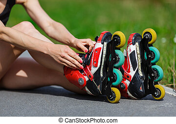Young girl putting on inline skates