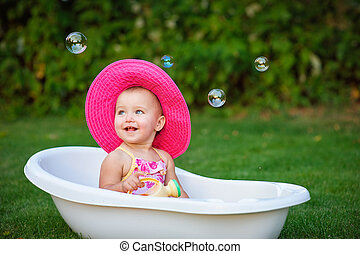 little girl in a red hat bathed in the bath.