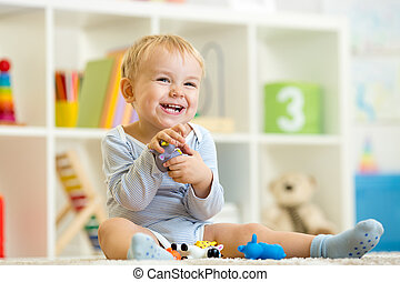 little child plays with toys animals at home