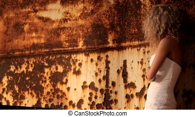 Bride Stands Next To A Rusty Wall - The bride in a wedding...