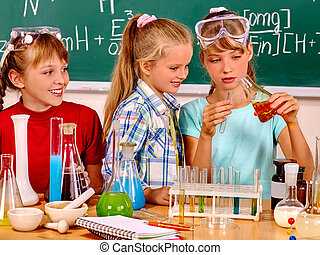Child in chemistry class - Happy child holding flask in...