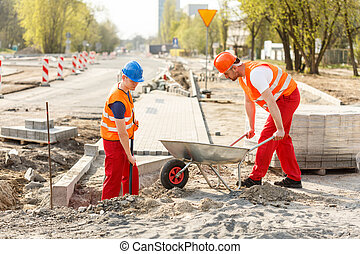 Construction workers repairing road - Male construction...