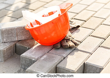 Orange safety helmet lying on paving stones