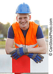 Young smiling builder wearing safety helmet and waistcoat